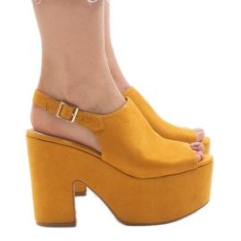 Sandálias amarelas em um maciço 8263CA tijolo amarelo